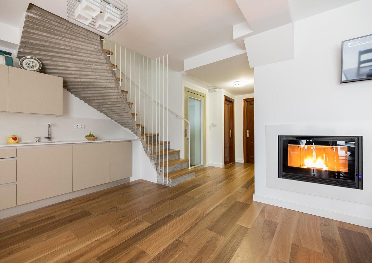 Salón de una vivienda de dos plantas, con escalera y chimenea.