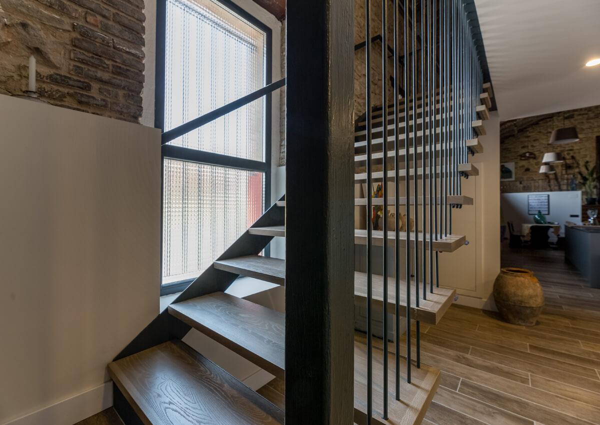 Detalle de una escalera de madera y metal.